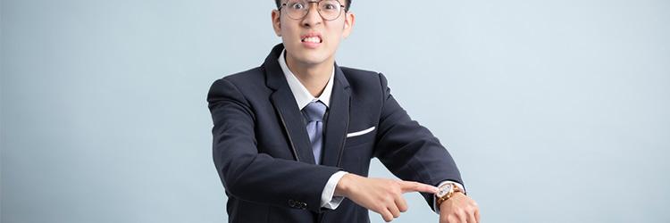 腕時計に指を当てて時間を気にする男性