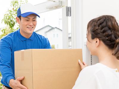 荷物の受け渡しをする配送業者と女性