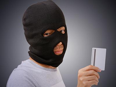 クレジットカードを手に持つ悪人゙